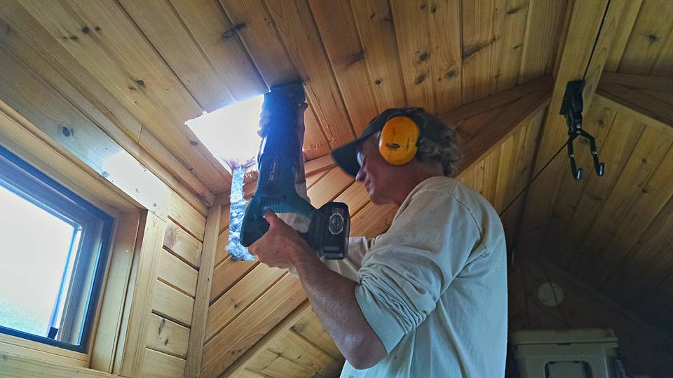 A photo of a chimney installation, cutting a hole in the ceiling.