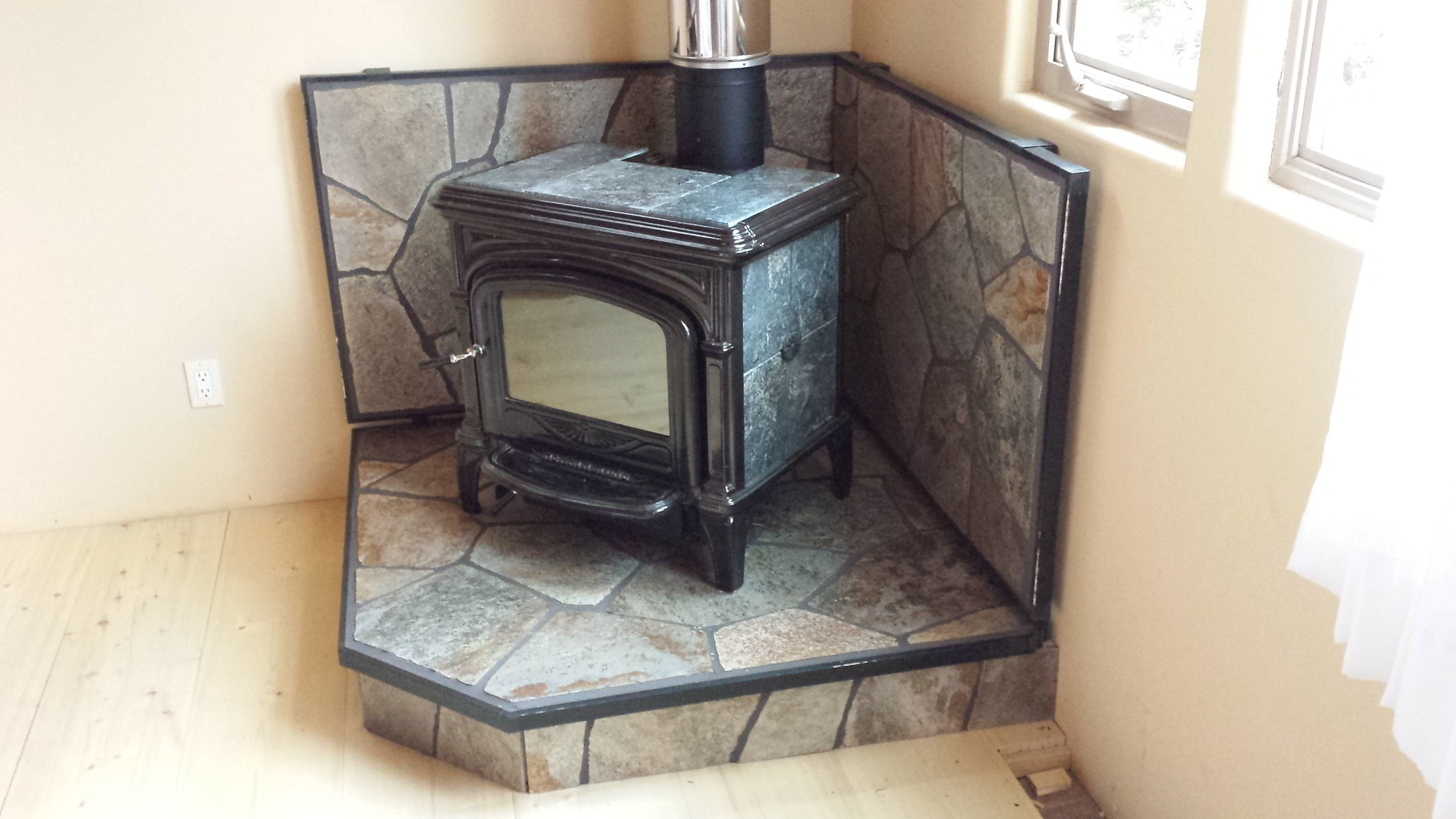 A wood burning stove with rock masonry heat guards installed by Shangrilah Stove LLC.